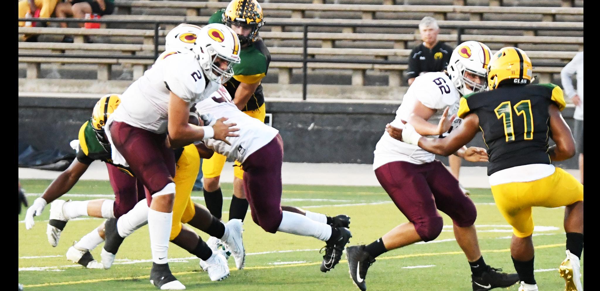 Clinton sophomore quarterback Caden Powell, No. 2, runs through a Lawton Mac tackle and follows Hudson Powell's block into the end zone.