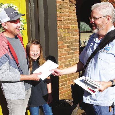 CDN I Robert S. Bryan Mail carrier Jimmy Ferrero delivers a U.S. Census form to Clinton resident Randy Jones and his daughter, fifth-grader Esme Jones.